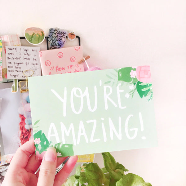 "Light green greeting card with pink and green floral decorations in the upper right and lower left corners. Written in white is the phrase ""YOU'RE AMAZING!"" in the middle."