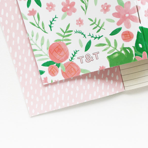 White pocket journal decorated with pink and green floral illustrations, recycled lined pages