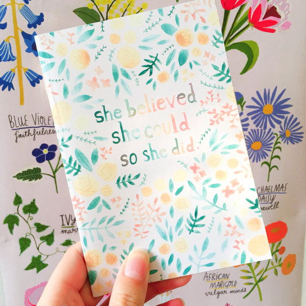 "Small light pink travel notebook decorated with colourful floral illustrations and the quote ""she believed that she could so she did"""