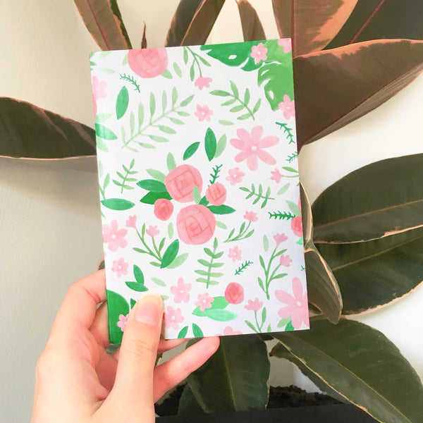 White pocket journal decorated with pink and green floral illustrations