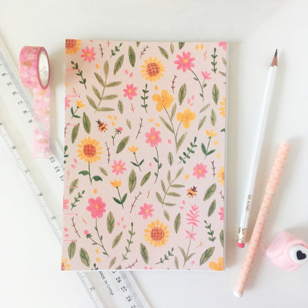 Light pink journal decorated with yellow, green and pink floral illustration. The journal is hand bound with light pink thread.
