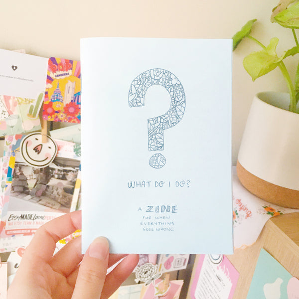 "A handmade zine printed on light blue paper. The cover has a large question mark decorated with flowers, and reads ""What Do I Do? A zine for when everything goes wrong."""