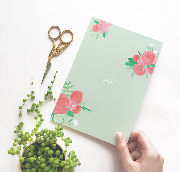 "Light green bullet journal decorated with pink and green floral illustrations, and featuring the quote ""rest"" on the cover"