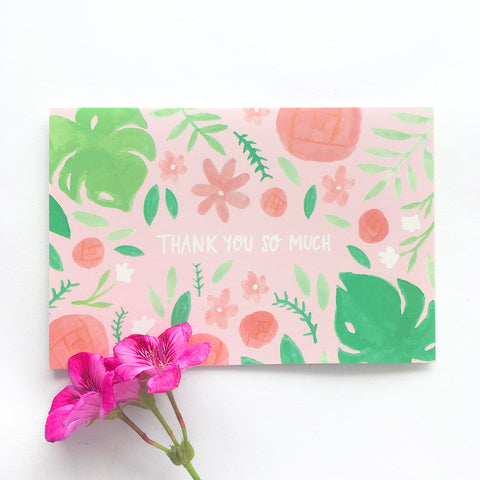 "Pink greeting card with pink and green floral illustrations and the words ""THANK YOU SO MUCH"" in white."