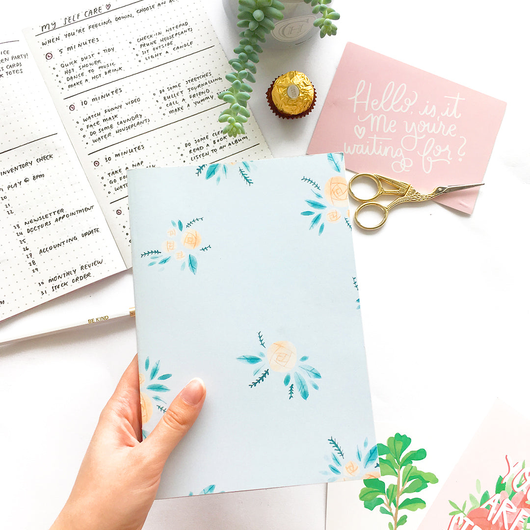 Light blue journal decorated with yellow and blue floral pattern