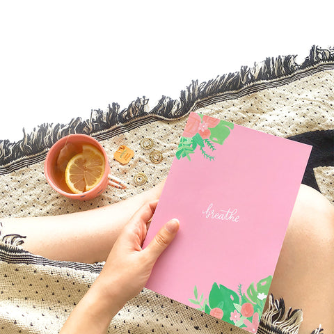 "Dark pink bullet journal decorated with pink and green floral illustrations and featuring the quote ""breathe"" on the cover"