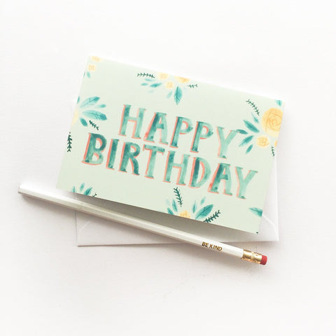 Light green greeting card with yellow and green watercolour floral illustrations and the words HAPPY BIRTHDAY in the centre.