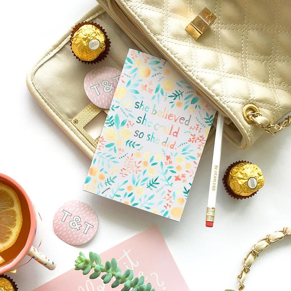 "Small light pink pocket journal decorated with colourful floral illustrations and the quote ""she believed that she could so she did"""