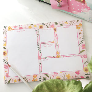 "Weekly planner pad with sections divided up for ""My Week"", ""Grateful For"", ""Self Care for This Week"", ""Notes"" and ""To Do"". The sections are white with pink outlines, and the background of the page with cream with yellow, green and pink floral illustrations."