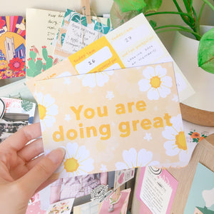 "Hand holding up a  yellow postcard in front of a colourful background filled with arts and a houseplant. The postcard features a print on a yellow background with white flowers and orange text that reads ""You are doing great"". Another copy of the postcard held behind it shows the back side which has a different design."