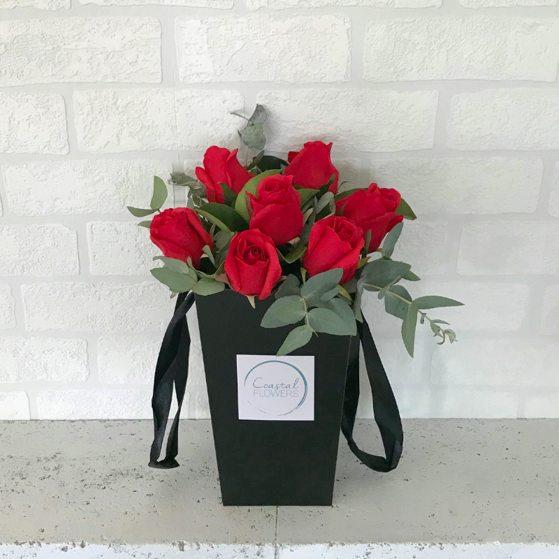 6 red roses displayed in our signature posy bag