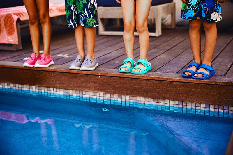 Kids in sandals and sneakers next to swimming pool