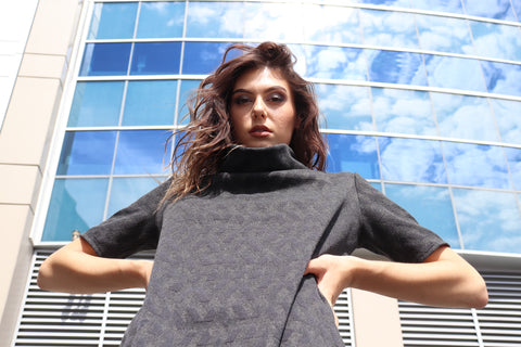 Woman wearing a grey/blue sweater dress made with dead stock fabric in front of a glass  building reflecting the sky of Seattle