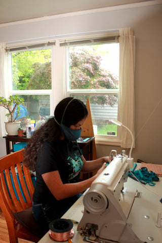 Sewing masks on the sewing station with a window on the background