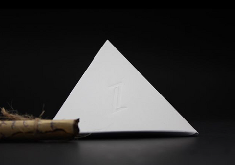 ZENPUI packaging, a white cardboard pyramid with a Z symbol on relief and a hand written blessing with burn edges, rolled and tied with a hemp rope