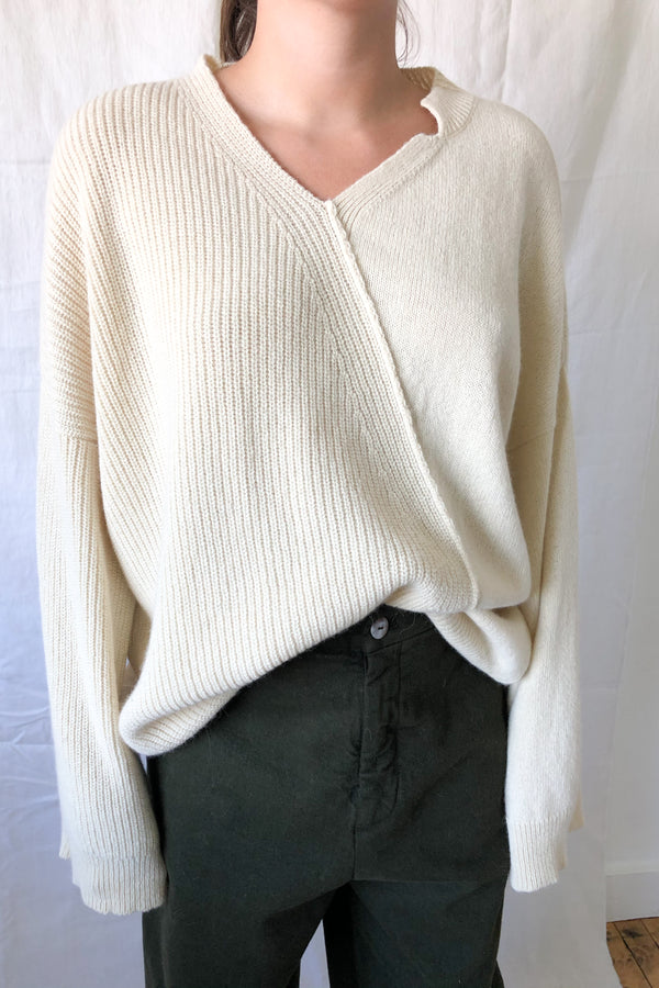 Ivory colored sweater designed with an oversize fit and an asymmetric v-neckline and diagonal front seam.