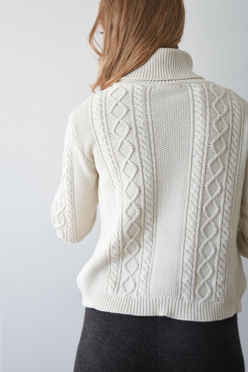 Vintage silk and cotton blend cable knit turtleneck sweater in ivory with ribbing at neck, sleeve and hemline.
