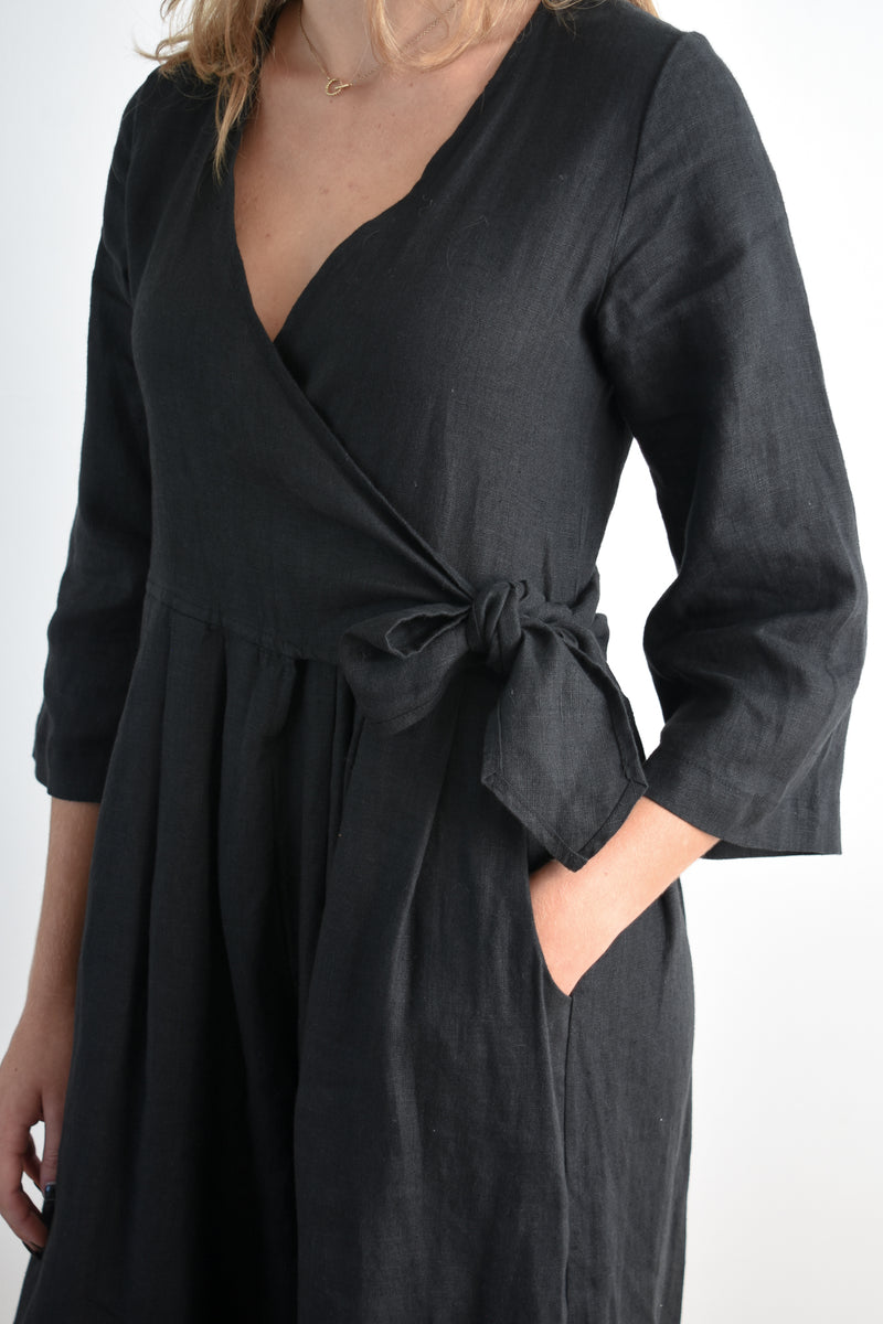 Sugar Candy Mountain Marigold Jumpsuit. Black linen jumpsuit featuring a wrap top, mid-length sleeves and pleated wide-legs bottoms with hidden pockets.