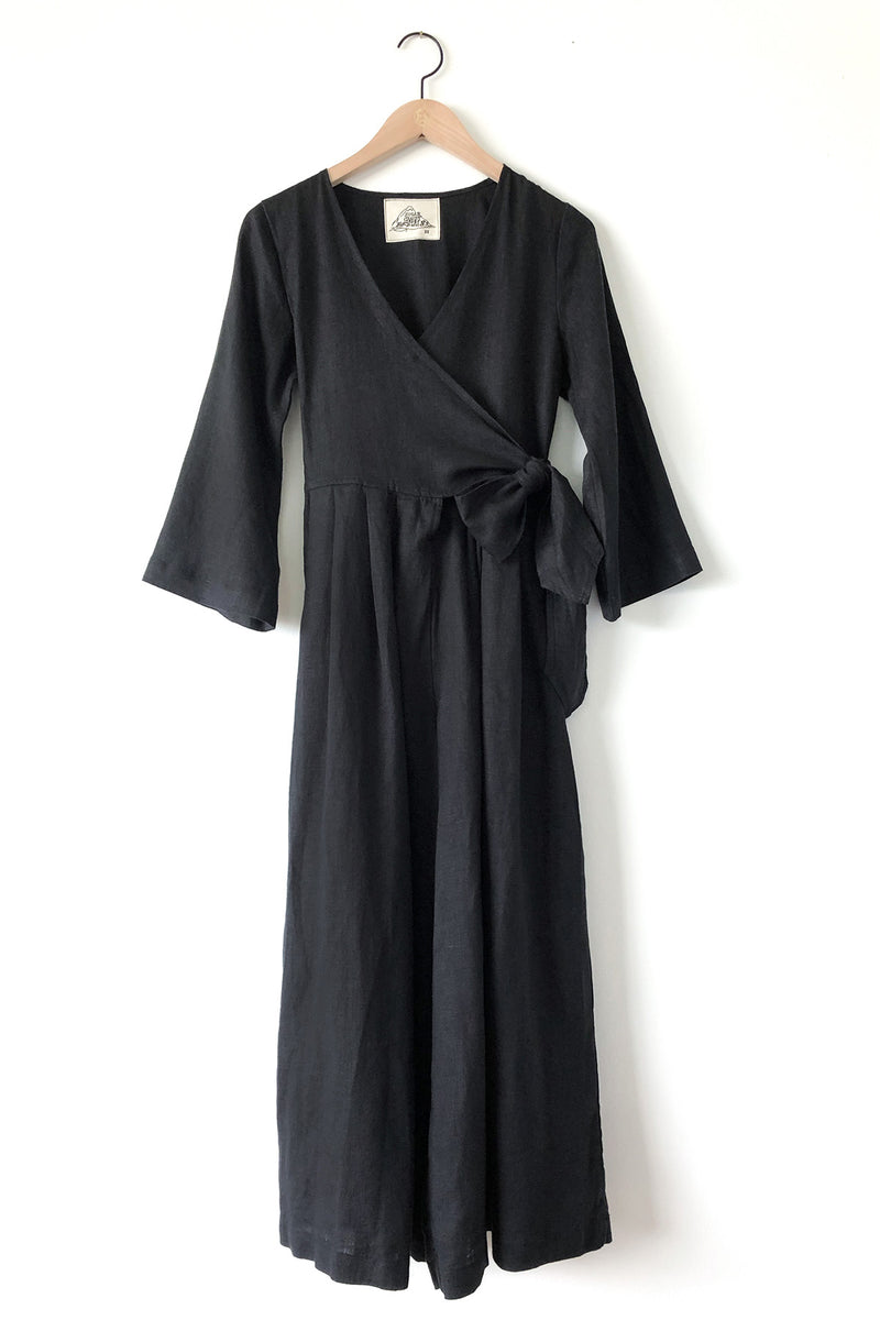 Black linen jumpsuit featuring a wrap top, mid-length sleeves and pleated wide-legs bottoms with hidden pockets. This wrap jumpsuit is designed to be slightly fitted at the bust and ties at the side for an adjustable look.Sugar Candy Mountain Marigold Jumpsuit. Black linen jumpsuit featuring a wrap top, mid-length sleeves and pleated wide-legs bottoms with hidden pockets.