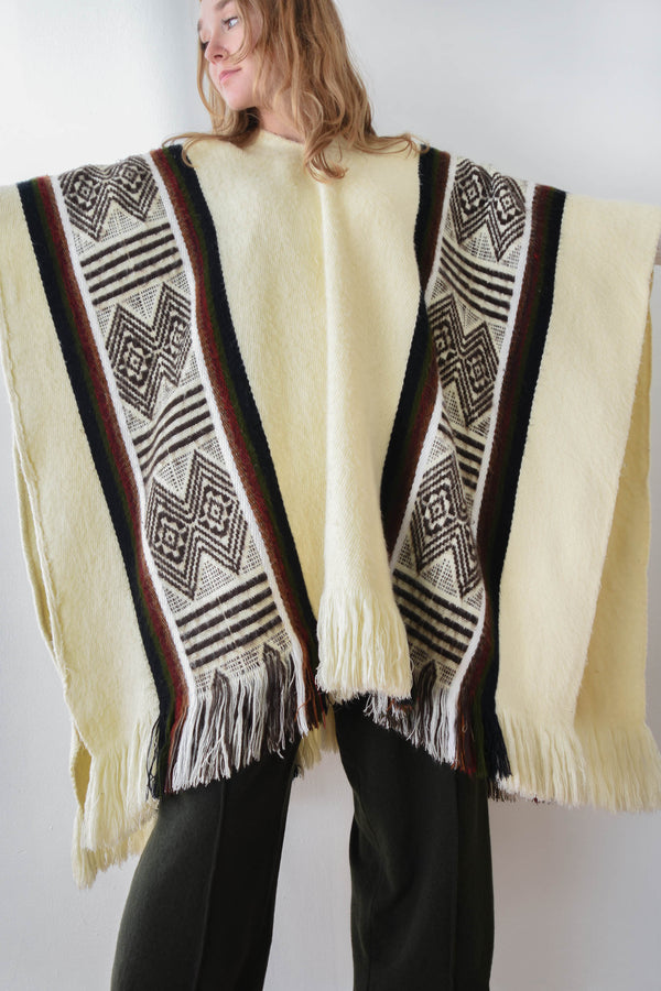 Soft and cozy vintage cream colored poncho with a woven geometric motif and vertical stripes. V-neckline and open at sides.