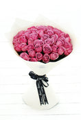 50 Long Stem Purple Roses Hand-Tied. Floral Bouquet in off-white packaging. Get fresh flowers from Flowers.IE. Same day flower delivery available.