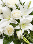 Rose and Lily Spray White. Aralia leaves and French Ruscus are nestled amongst classic Oriental lilies and large-headed roses in this classic teardrop spray. Have fresh flowers sent to you by Flowers.IE. Same day flower delivery available.