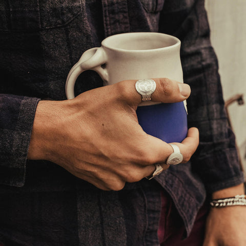 Man holding coffee mug with Air and Anchor jewelry on.