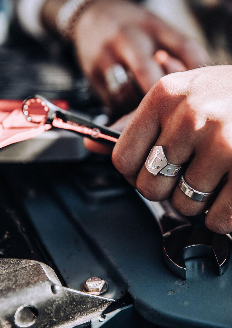 Man working on car wearing AIR AND ANCHOR sterling silver anchor cigar band ring