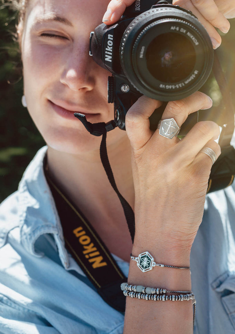 Woman holding camera wearing AIR AND ANCHOR jewelry
