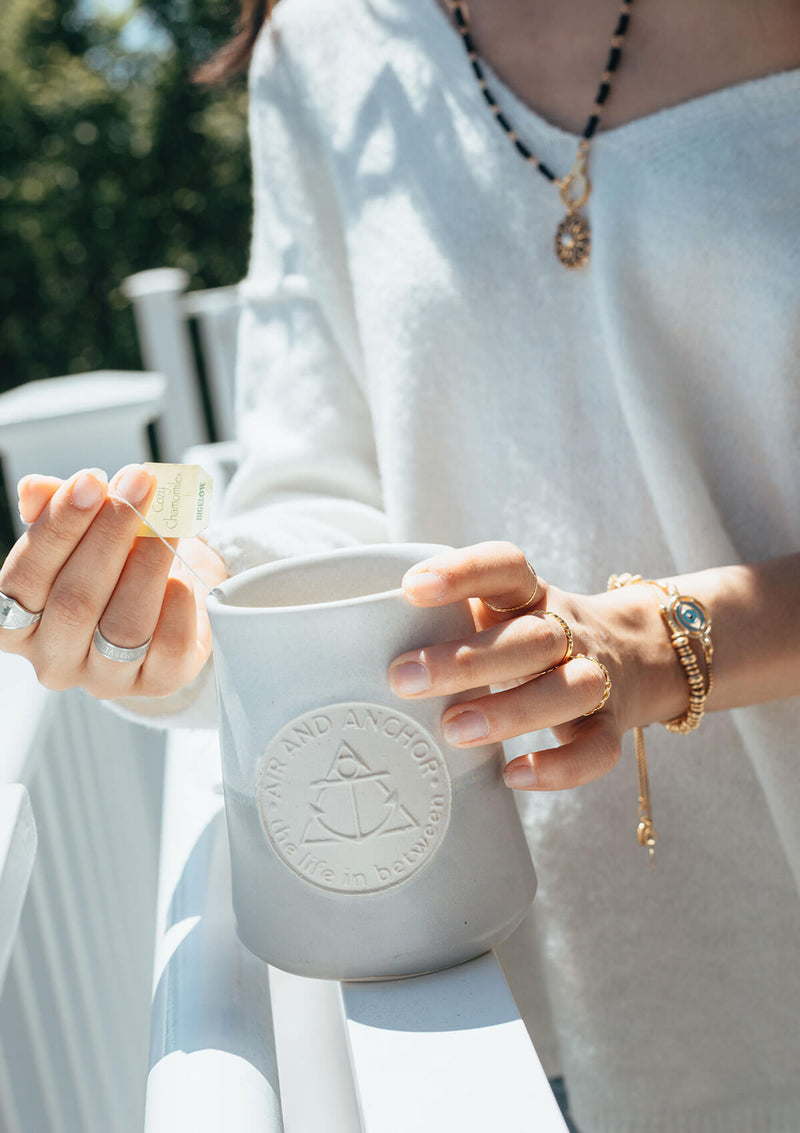 Woman drinking tea from the Big Ass Mug in Grey while standing on the porch wearing AIR AND ANCHOR jewelry.