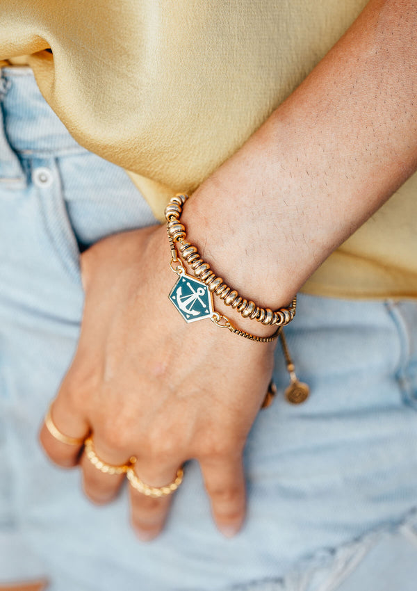 Woman's wrist in pocket with AIR AND ANCHOR metal beaded bracelet layered with anchor charm bracelet.