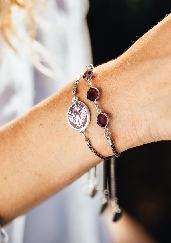 AIR AND ANCHOR's purple scarab adjustable charm bracelet in silver on a woman's wrist.