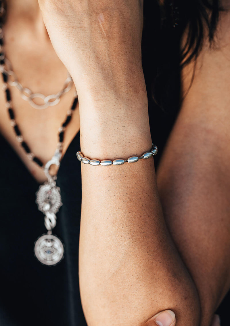 Woman wearing AIR AND ANCHOR isla metal beaded bracelet