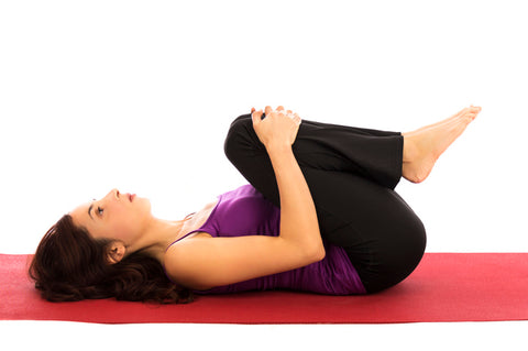 Knee to chest yoga pose for reducing stomach pain during periods instantly