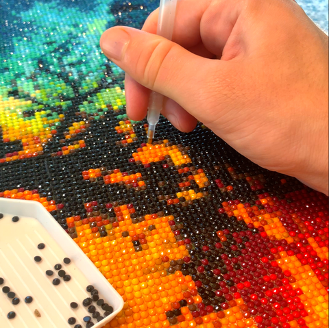 A hand making a diamond painting.