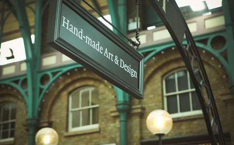 A sign that says hand-made art and design.