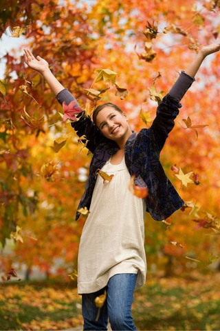 girl throwing leaves in the air