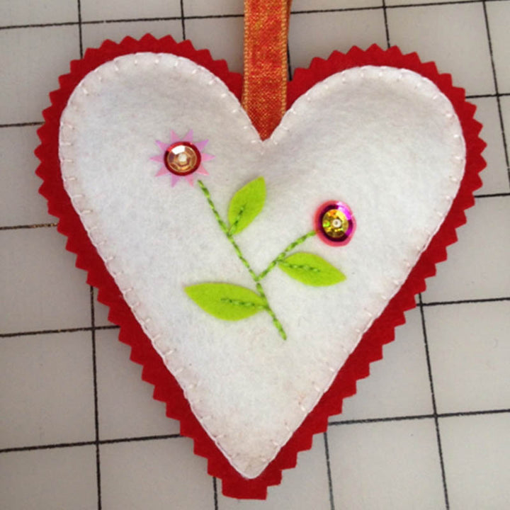 A white felt heart sachet trimmed in red with a flower design in the center from Fish Museum and Circus.