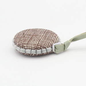 Retractable tape measure hand covered in linen