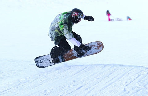 A snowboarder freestyling in the snow.