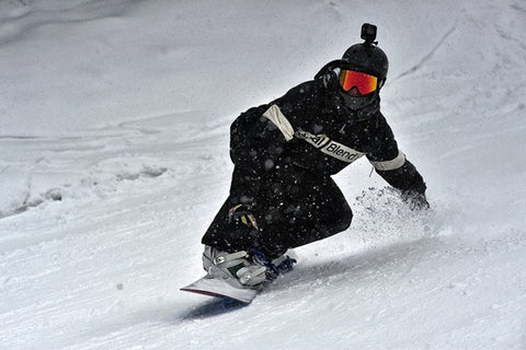 A snowboarder surfing on snow.