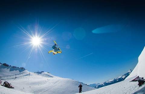 A skiing enthusiast flying off on a snowboard.