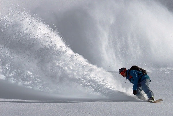 An enthusiastic snowboarder having a great time.
