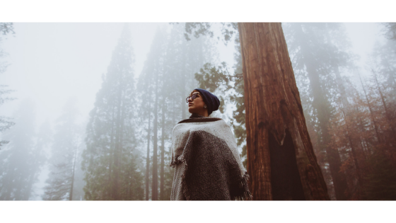 woman wrapped in a blanket standing in a misty forest