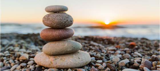 A zen stacked rocks overlooking the ocean sunset in preparation of anxiety breathing