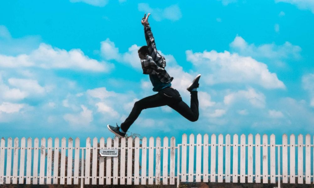 A adolescent boy jumping over fence with white background forgetting anxiety due to taking ashwagandha supplements