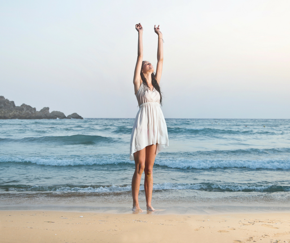Woman on beach with hands held high towards sky with beautiful ocean background