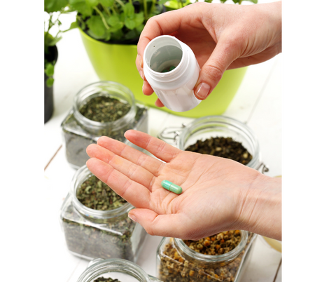 Hands showing a supplement bottle and green supplement pill, surrounded by natural herbs