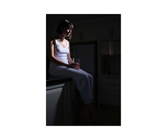 Woman With Fatigue in a dark corner dim silhouette of head down