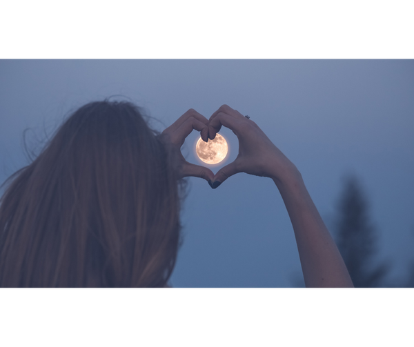 Woman framing the moon in heart-shaped hands